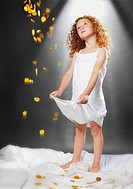 Girl catching shower of gold coins in dress