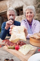 Italy, South Tyrol, Mature couple having their snacks at mountain hut