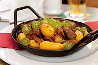 Goulash with salt potatoes and grapes in pan