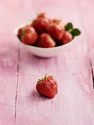 Strawberries in bowl on table, close up