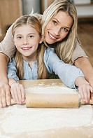 Germany, Cologne, Mother and daughter rolling dough, smiling, portrait
