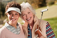 Italy, Kastelruth, Golfers on golf course, smiling, portrait
