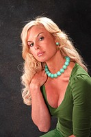 Beautiful blond model displaying an exotic jade set of matching necklace and earrings