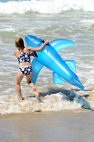 Six year old girl playing in the surf on inflatable shark  Mimiwhangata  Northland, New Zealand