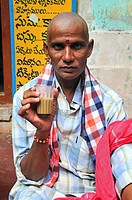 Man having tea by the narrow street in the old town
