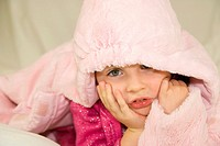 4 years old girl in pink clothing lying under the hood.