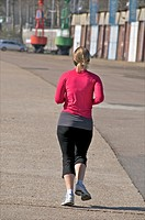 Young woman in red and black jogging along a harbour wharf