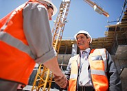 Construction workers shaking hands on construction site (thumbnail)