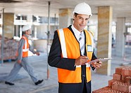 Construction worker holding clipboard on construction site