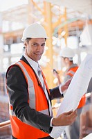 Businessman looking at blueprints on construction site