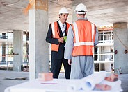 Businessman talking to construction worker on construction site