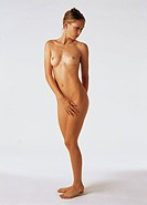 Nude woman standing and turning backwards