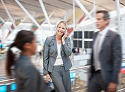 Businesswoman talking on cell phone in airport