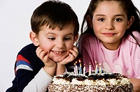 boy and girl sitting in front of a birthday cake