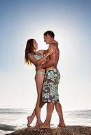 Couple hugging on rock near ocean