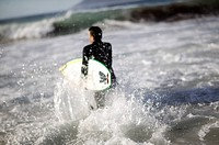 man wearing a wet suit walking in the water with a windsurfing board under his arm