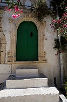Italy, Puglia, Ostuni, green front door of house with steps