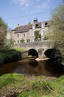 England, Derbyshire, Baslow, arch bridge over river with houses in background