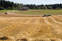 Germany, Bavaria, harvesting field in countryside