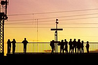 Abstract pattern of silhouettes of travellers at a suburban train station in the glow of early evening