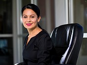 Hispanic businesswoman sitting in chair