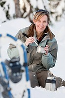 Caucasian woman with snowshoes eating in snow