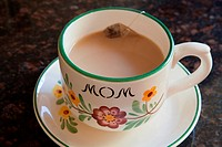 Teacup and saucer with 'mom' written on it