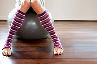 Woman wearing stripey legwarmers sitting on exercise ball