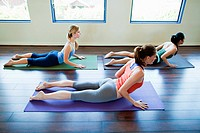 Three woman doing cobra pose in yoga class