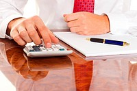 Businessman with a calculator. Calculation of costs, revenues, balance sheet