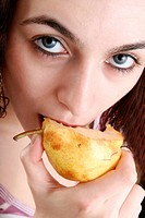 Hungry woman eating a pear