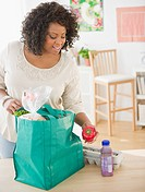 African American woman unloading groceries