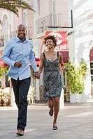 African American couple holding hands and running