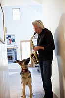 Dog listening to Caucasian man play saxophone