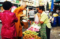 A Buddhist monk collects food from the woman vendor at Kao San Road market Bangkok, Thailand October 31, 2005