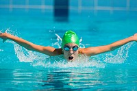 Swimmer swimming butterfly stroke in pool water