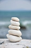 Stack of balanced stones on rock with sea in background