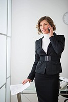 USA, New Jersey, Jersey City, businesswoman talking on mobile in office