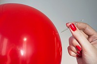 Close up of red balloon and woman´s hand holding needle