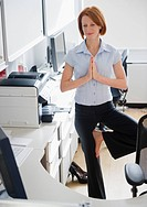 USA, New Jersey, Jersey City, businesswoman doing yoga position in office