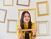 USA, Jersey City, New Jersey, portrait of woman holding picture frame over face