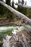 A male kayaker surfs some rapids on the Highwood River, Alberta, Canada