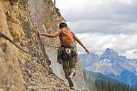 A woman rockclimber climbs Takakaw Falls 5.6, Yoho National Park, British Columbia, Canada