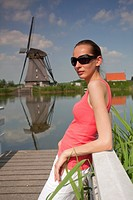 woman on wooden pier and windmill
