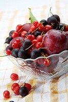 Mixed summer splitted berries in a cristal bowl on white