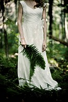 Woman in Wedding Dress Holding Fern in Forest