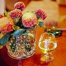 A glass of cognac and dahlias in a vase.