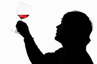 A silhouetted man holding up a glass of red wine to examine it