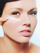 A woman applying moisturizer on her cheek