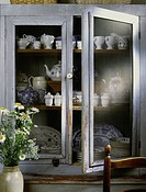 Detail of cottage chic weathered light blue grey pie safe cabinet, antique blue and white china & teapots with crock of daisies on left